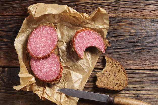 Simple sandwich with salami and rye bread on kitchen board, top view