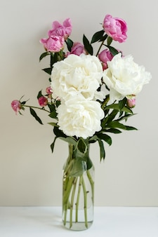 Simple sloopy flower bouquet of pink and white peonies flowers in a transparent vase over pastel background, spring and summer season flowers, valentine`s day
