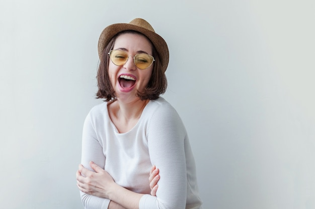 Simple studio portrait of hipster fashion smiling girl in trendy yelow sunglasses and hat isolated on white