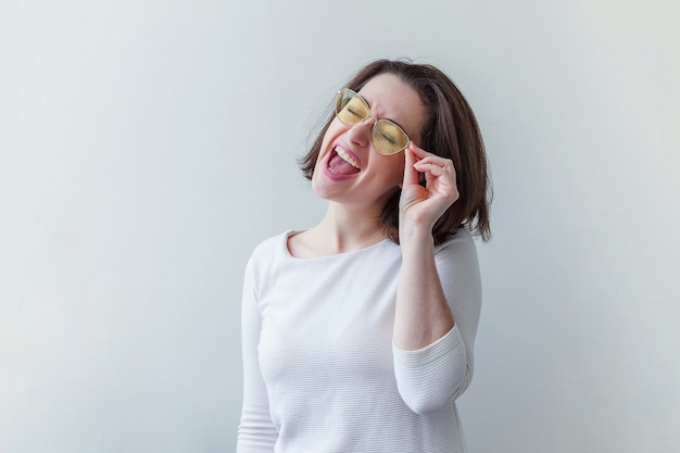 Простой студийный портрет хипстерской модной улыбающейся короткошерстной брюнетки в модных желтых солнцезащитных очках, изолированной на белом