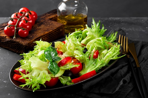 블랙 플레이트 클로즈업에 올리브와 올리브 오일을 곁들인 양상추 토마토의 간단한 여름 샐러드