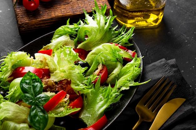검은 접시에 올리브와 올리브 오일을 곁들인 양상추 토마토의 간단한 여름 샐러드