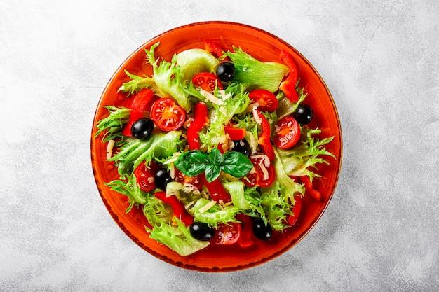 붉은 접시와 밝은 회색에 올리브와 올리브 오일을 곁들인 양상추 토마토의 간단한 여름 샐러드