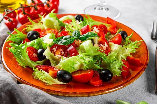 빨간 접시 클로즈업에 올리브와 올리브 오일을 곁들인 양상추 토마토의 간단한 여름 샐러드