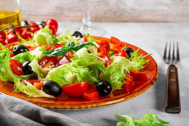빨간 접시에 올리브와 올리브 오일을 곁들인 양상추 토마토의 간단한 여름 샐러드
