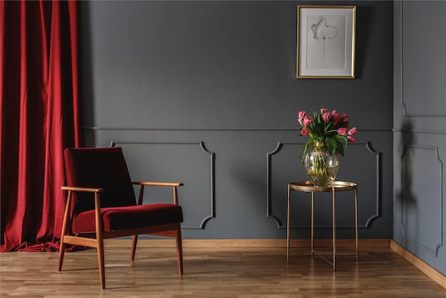 Simple waiting room interior with a single red armchair standing against dark gray wall with molding next to a golden table with pink flowers. real photo
