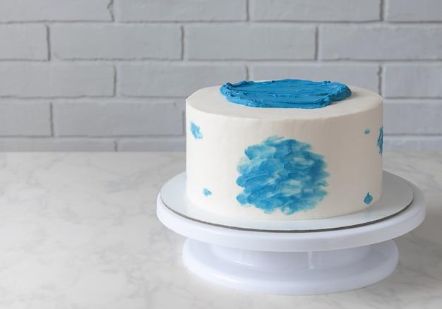 テーブルの上に青い装飾が施されたシンプルな白いケーキ。