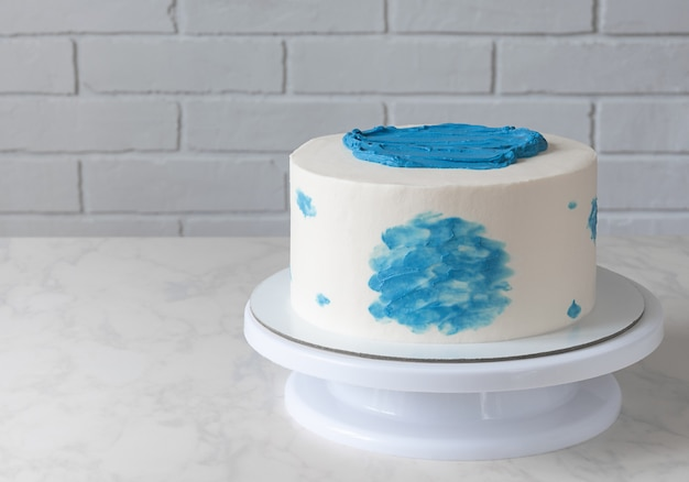 Simple white cake with blue decor on table.