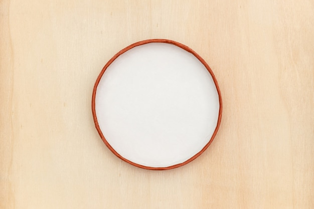 Simple white circle frame on wooden surface