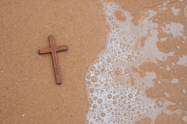 Простой деревянный крест на фоне песка