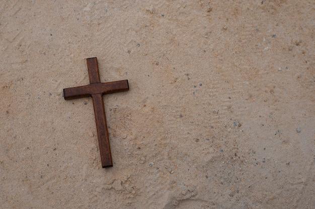 Simple wood cross on sand background