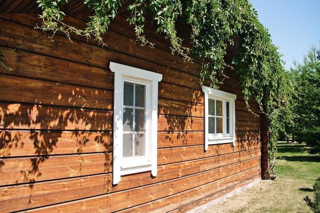 Простой деревянный бревенчатый коттедж в солнечный летний день стена гостевого дома с двумя окнами