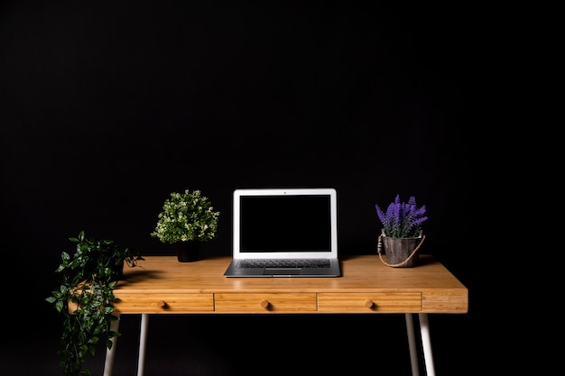 Simple wooden desk with gray laptop