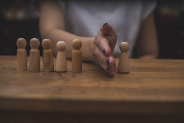 Simple wooden figures are being separated by a hand