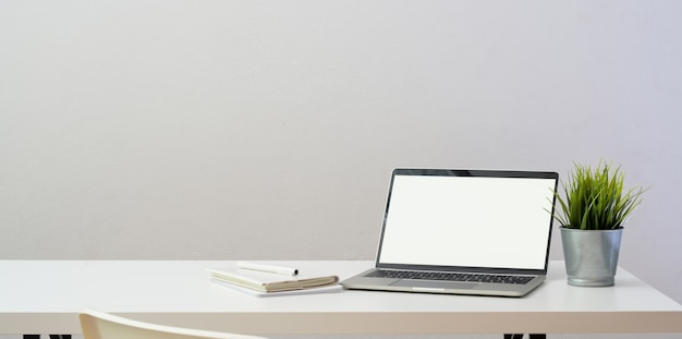 Simple workplace with open blank screen laptop computer and decorations