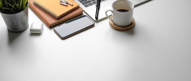 コピースペース、ラップトップ、コーヒーカップ、スマートフォン、スケジュール帳、植木鉢のあるシンプルなワークスペース