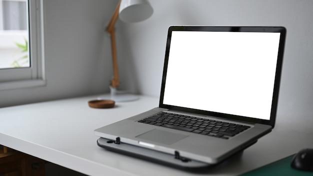 흰색 나무 테이블에 노트북으로 간단한 작업 공간 그래픽 디스플레이 몽타주에 대한 빈 화면.