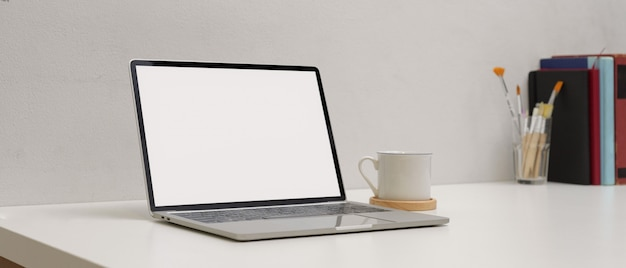 Простое рабочее пространство с макет ноутбука, чашки, копировать пространство живописи кисти и книги на белом столе