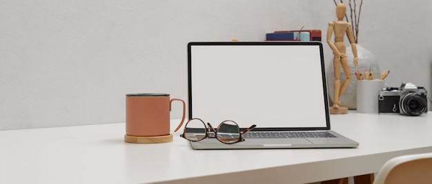 Simple worktable with mock up laptop, glasses, mug and supplies on white table with white chair