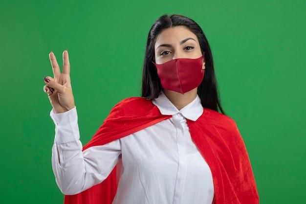 Простая молодая кавказская девушка супергероя в маске делает знак мира, глядя в камеру, изолированную на зеленом фоне