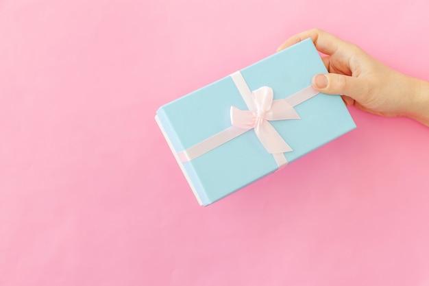 ピンクのテーブルで隔離の青いギフトボックスを持っている女性の女性の手をシンプルにデザイン