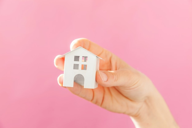 ピンクのパステル調のカラフルなトレンディな背景に分離されたミニチュア白いおもちゃの家を持つ女性の女性の手を単にデザイン