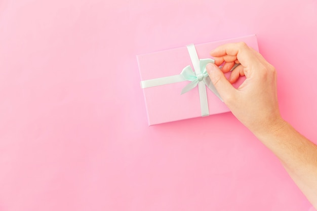 Simply design female woman hand holding pink gift box isolated on pink pastel colorful trendy background