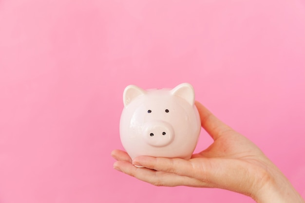 Simply design female woman hand holding pink piggy bank isolated on pink pastel colorful trendy background