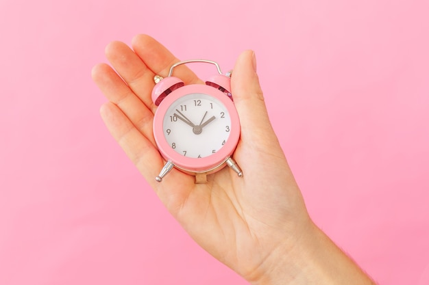 Simply design female woman hand holding ringing twin bell alarm clock isolated on pink table