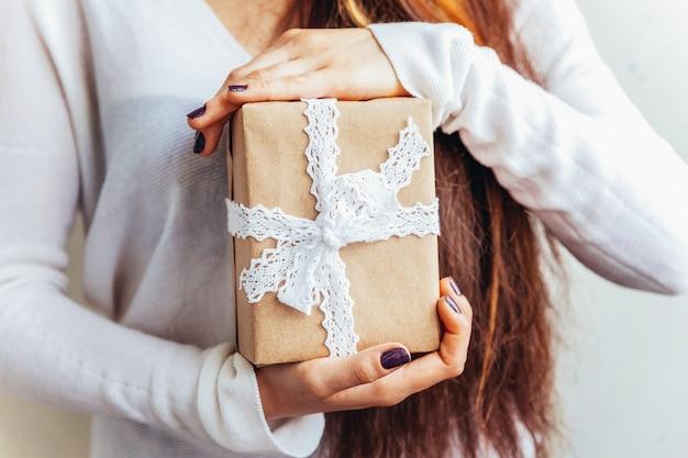 単に白い背景で隔離のヴィンテージ茶色のギフトボックスを持っている女性の女性の手を設計します。クリスマス新年誕生日バレンタインのお祝いはロマンチックなコンセプトを提示します。