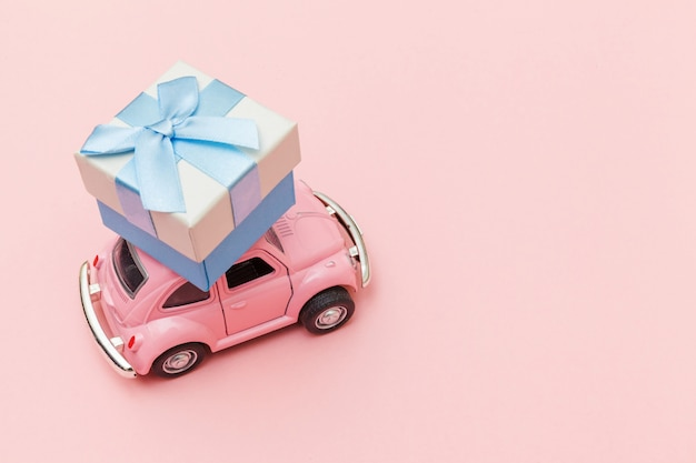 Simply design pink vintage retro toy car delivering gift box on roof isolated on trendy pastel pink background. christmas new year birthday valentine's day celebration present romantic concept