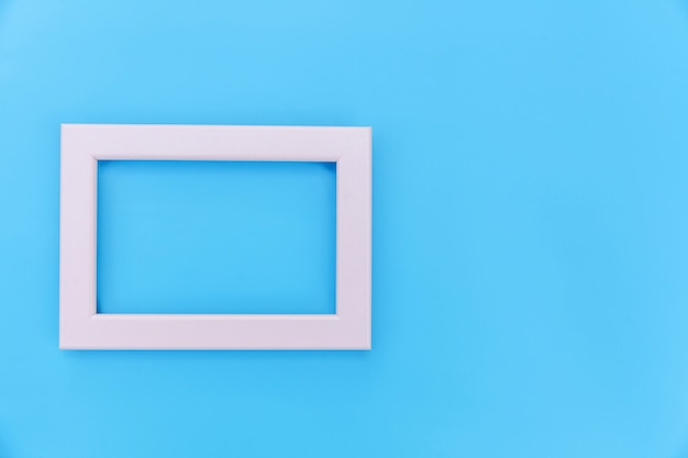 Simply design with empty pink frame isolated on blue pastel colorful background. top view, flat lay, copy space, mock up. minimal concept.