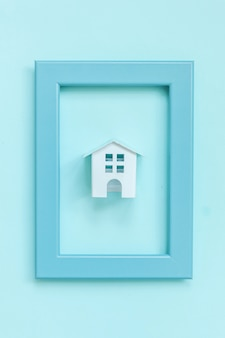 Simply design with miniature white toy house in blue frame isolated on blue pastel colorful