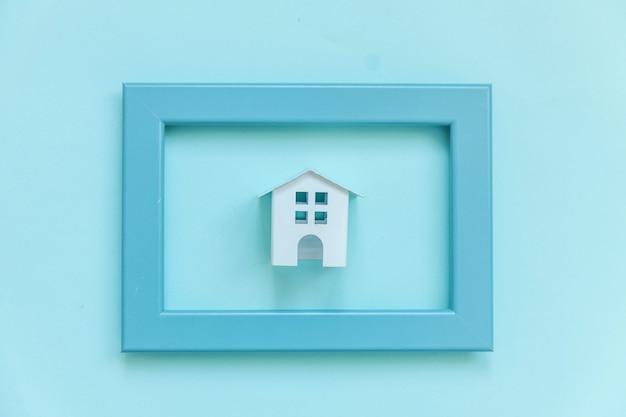 青いパステルカラーのカラフルなトレンディな背景に分離された青いフレームのミニチュア白いおもちゃの家で単にデザイン