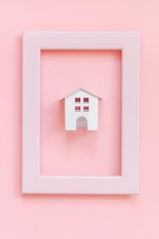 ピンクのパステル調のカラフルなトレンディな背景に分離されたピンクのフレームのミニチュア白いおもちゃの家で単にデザインする