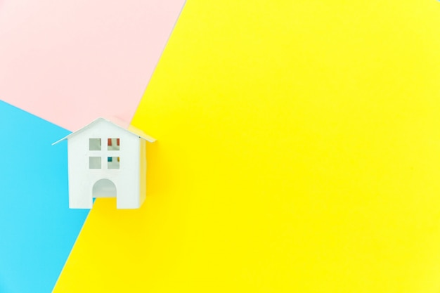 Simply design with miniature white toy house isolated on blue yellow pink background