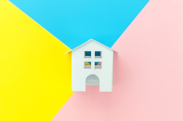 Simply design with miniature white toy house isolated on blue yellow pink pastel colorful trendy geometric table mortgage property insurance dream home concept. flat lay top view copy space.