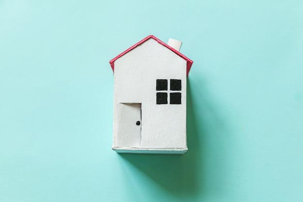 Просто дизайн с миниатюрным белым игрушечным домиком, изолированным на синей пастельной красочной модной стене. концепция дома мечты страхования ипотечного имущества. плоские лежал вид сверху копией пространства.