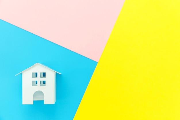 파란색 노란색 분홍색 파스텔 다채로운 기하학적 배경에 고립 된 미니어처 흰색 장난감 집으로 단순히 디자인