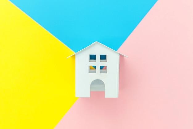 ブルーイエローピンクパステルカラフルなトレンディな幾何学的なテーブル住宅ローンの財産保険の夢の家のコンセプトで分離されたミニチュア白いおもちゃの家でシンプルにデザイン。フラットレイトップビューコピースペース。