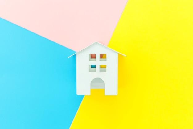 Простой дизайн с миниатюрным белым игрушечным домиком, изолированным на сине-желто-розовом