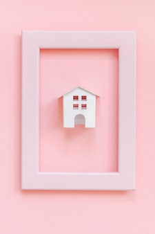 Simply design with miniature white toy house in pink frame isolated on pink pastel colorful trendy background