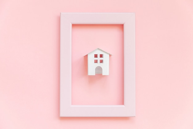 Simply design with miniature white toy house in pink frame isolated on pink pastel colorful trendy