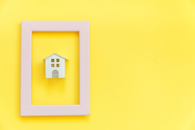 Simply design with miniature white toy house in pink frame