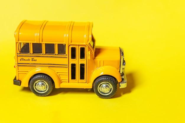 単に黄色のカラフルな背景に分離された黄色の古典的なおもちゃの車のスクールバスをデザインします。