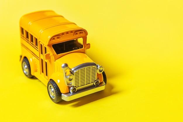 黄色のカラフルな背景に分離された黄色の古典的なおもちゃの車のスクールバスを単に設計する