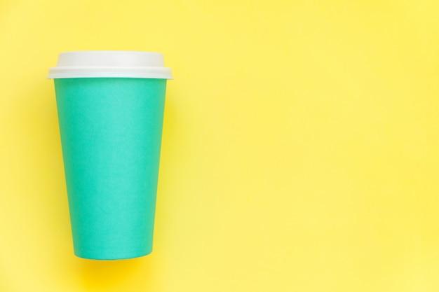 単にフラット横たわっていたデザイン青い紙コーヒーカップ黄色のカラフルなトレンディな背景に分離