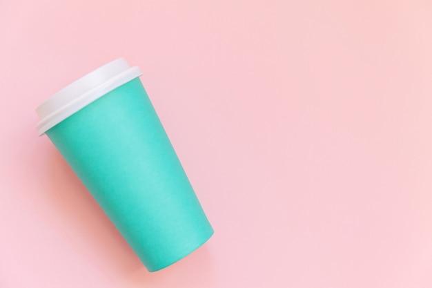ピンクのパステルカラーの背景にシンプルなフラットレイデザインの青い紙のコーヒーカップ