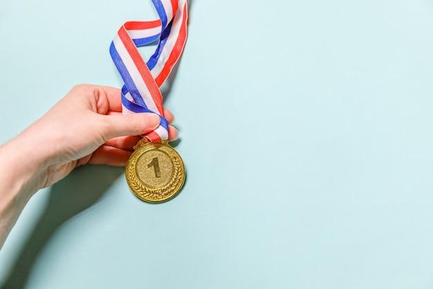 Просто плоская планировка рука держит победителя или чемпиона золотую трофейную медаль, изолированную на синем красочном фоне. победа за первое место конкурса. концепция победы или успеха. копирование пространства вид сверху.
