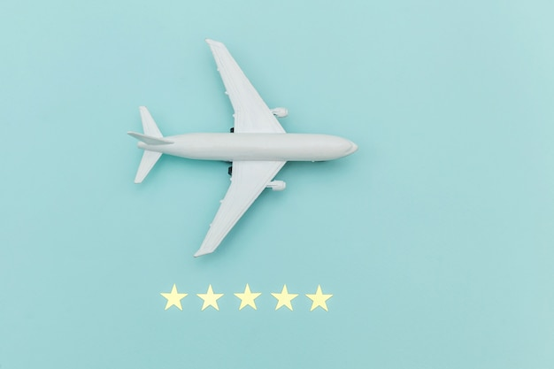 Simply flat lay design miniature toy model plane and 5 stars rating on blue pastel colorful trendy background. travel by plane vacation summer weekend sea adventure trip journey ticket tour concept.